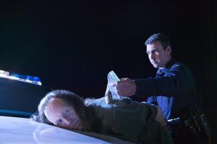 Close-up of a police officer making an arrest, bending the suspect over the hood of his police car and holding a bag of evidence