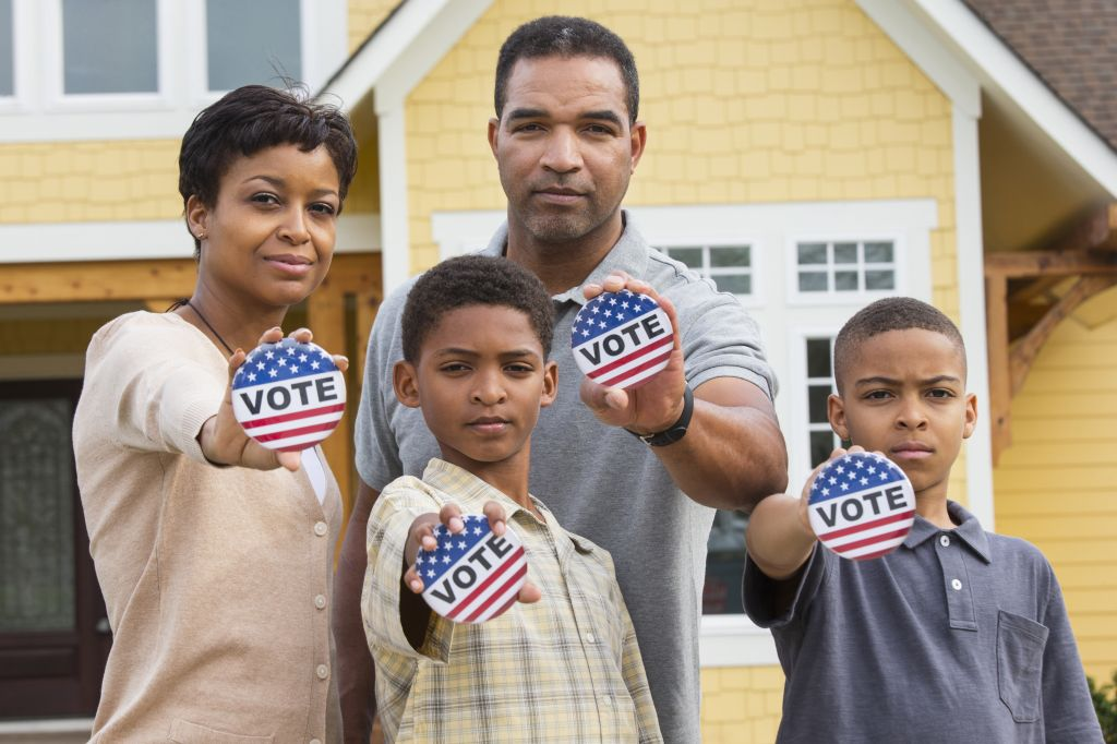 Black family holding Vote buttons outside home