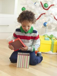 Young boy sitting under Christmas tree, opening Christmas presents