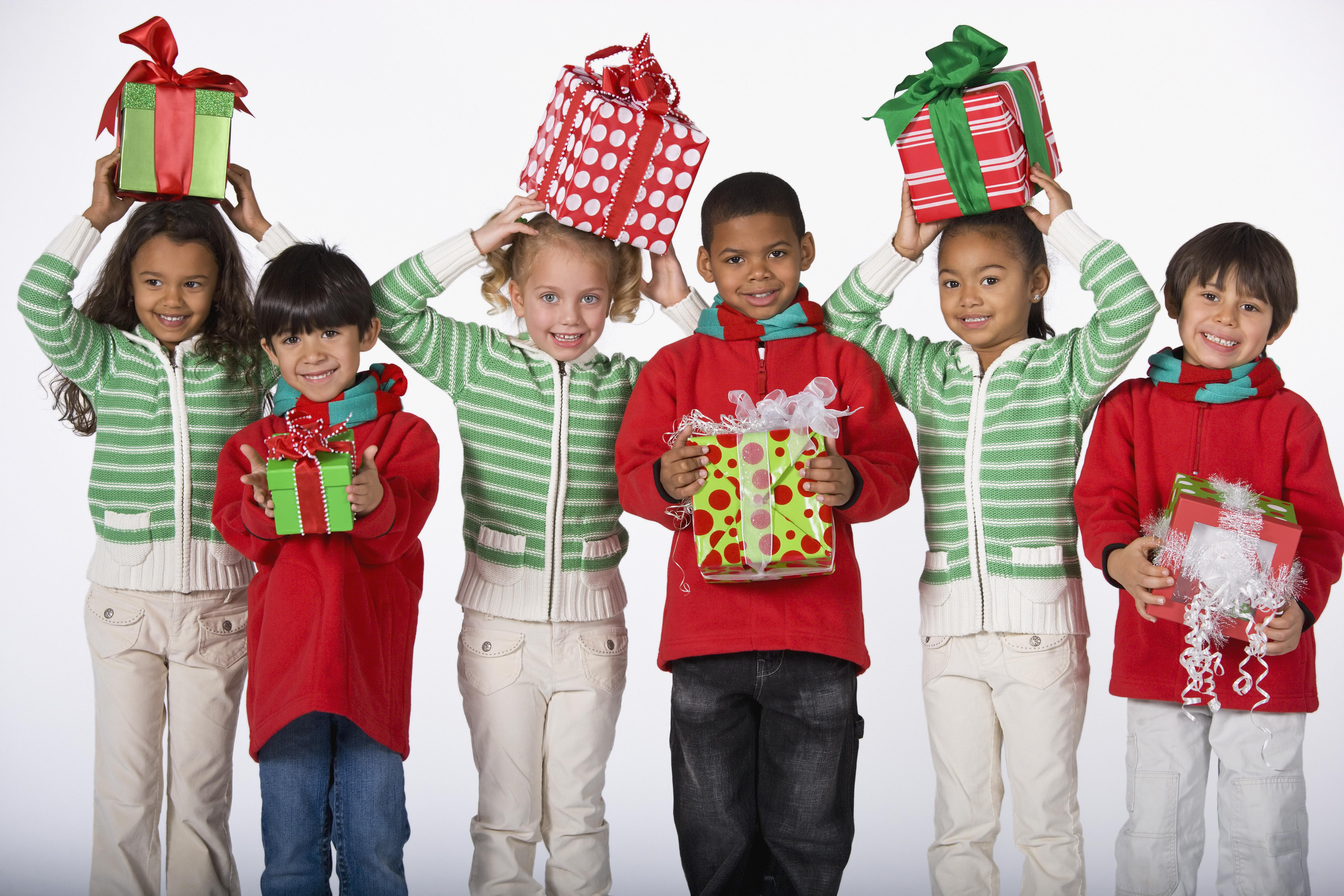 Multi-ethnic children holding Christmas gifts