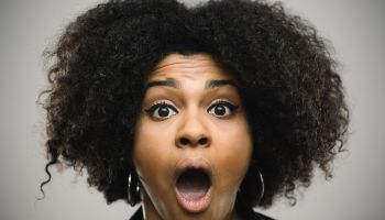 Close-up portrait of a shocked real young afro american woman