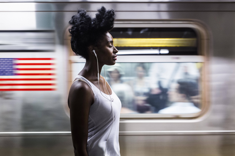 USA, New York City, Manhattan, woman with earphones on subway station platform
