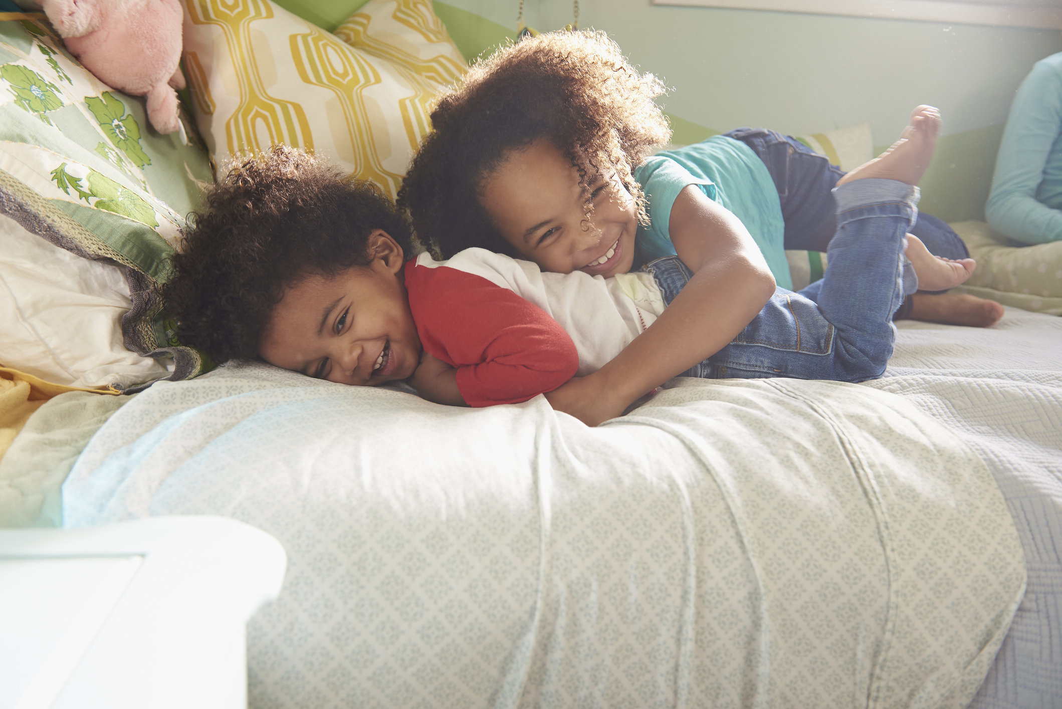 Smiling Black girl tickling baby brother on bed