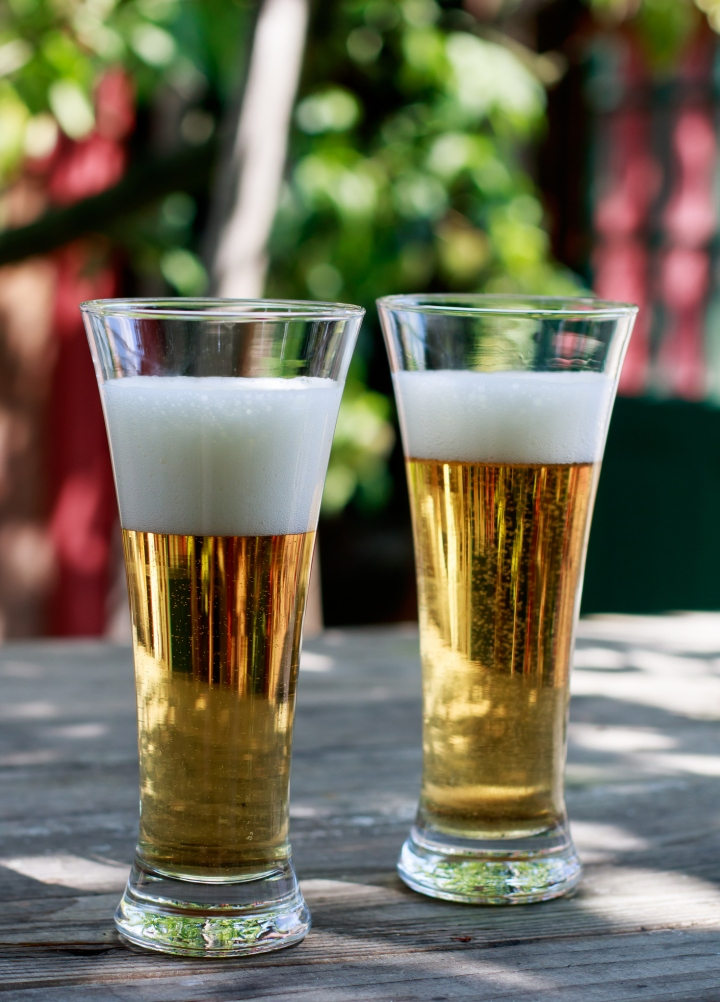 Two glasses of beer on a table in the garden
