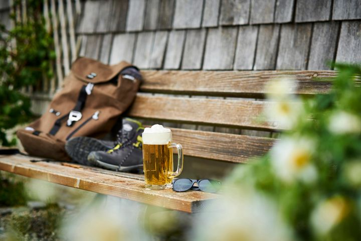 Germany, Bavaria, glass of beer, backpack, sunglasses and hiking shoes on wooden bench