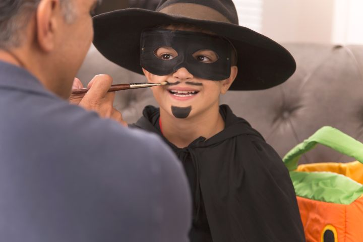 Little boy dresses up for Halloween with dad's help.