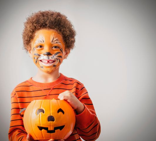 Mixed race boy with tiger costume and Halloween jack-o-lantern bucket
