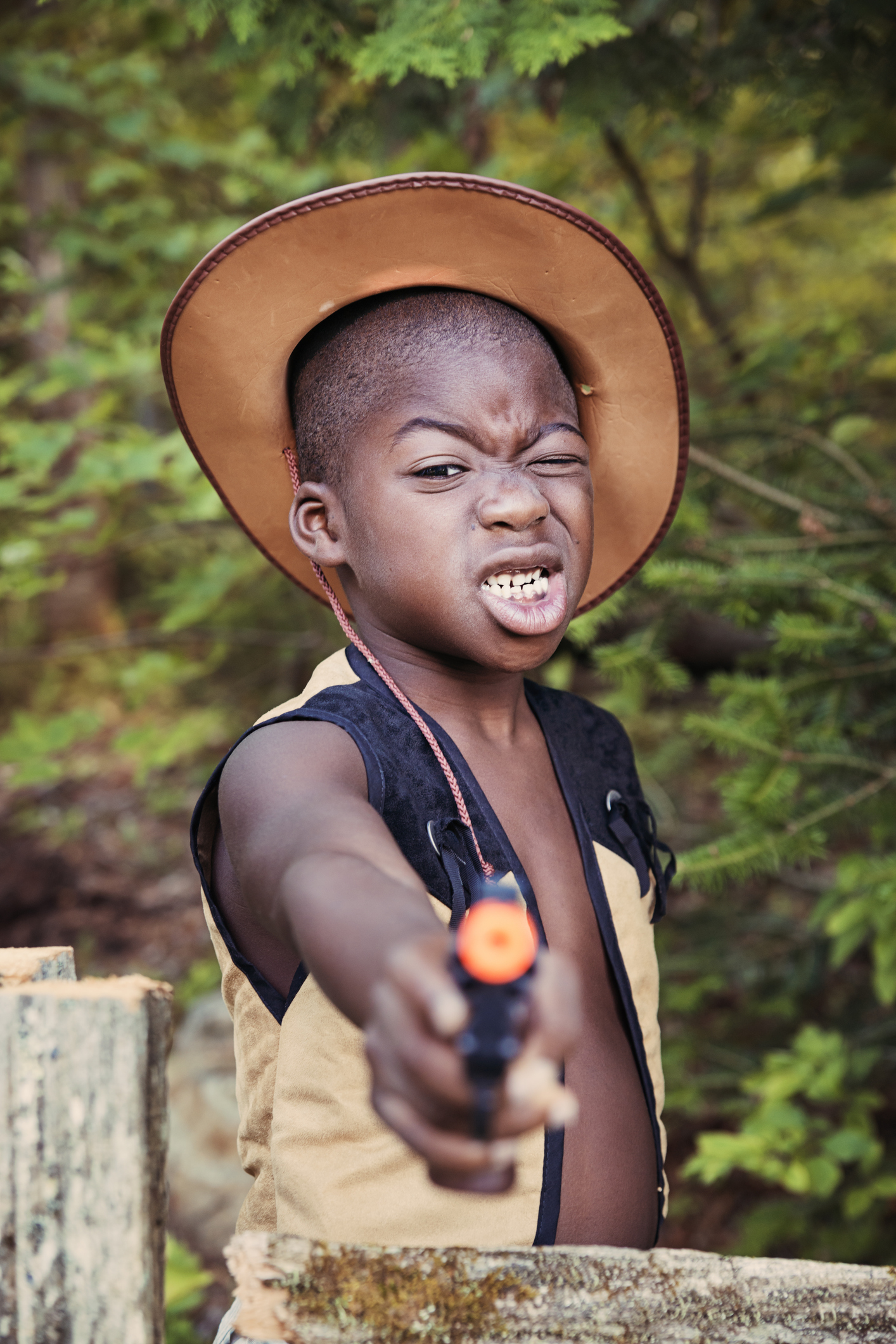 Little black boy playing cowboy with a toy gun.