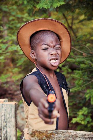 Little black boy playing cowboy with a toy gun.