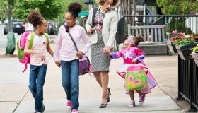 Mixed Race woman walking daughters to school in city
