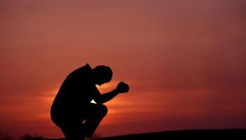 Silhouette of Man Praying at Dusk