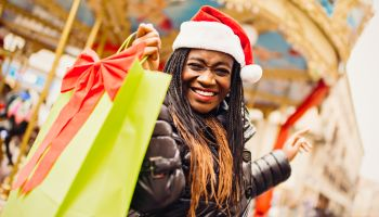 Young African woman in Santa hat with shopping bag