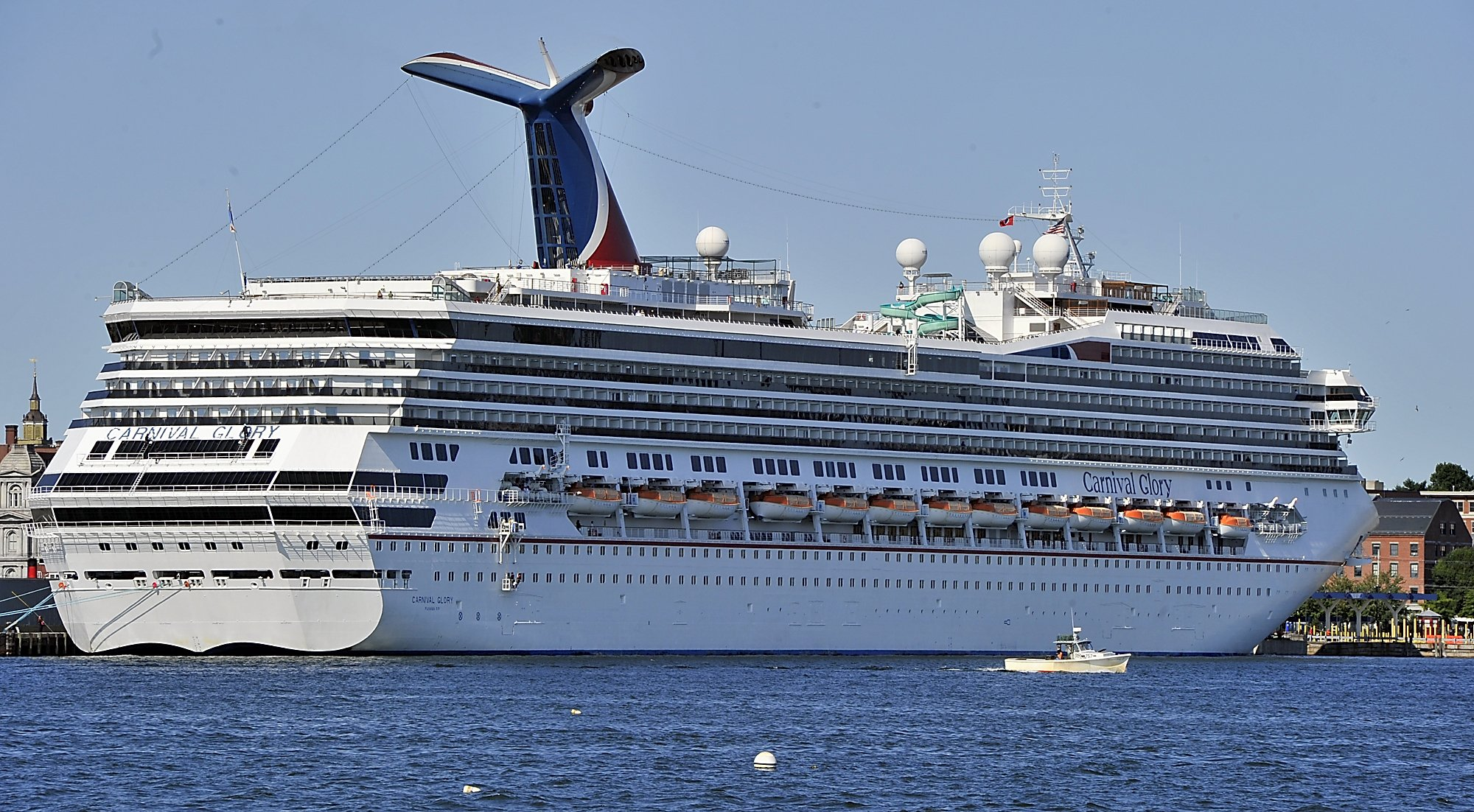 On Tuesday, September 17, 2013, a lobster boat is dwarfed by the size of the Carnival Glory, a cruis