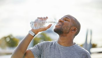 Tired man drinking water from bottle on sunny day