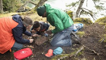 Trail guide teaching father and son how to build a campfire in woods