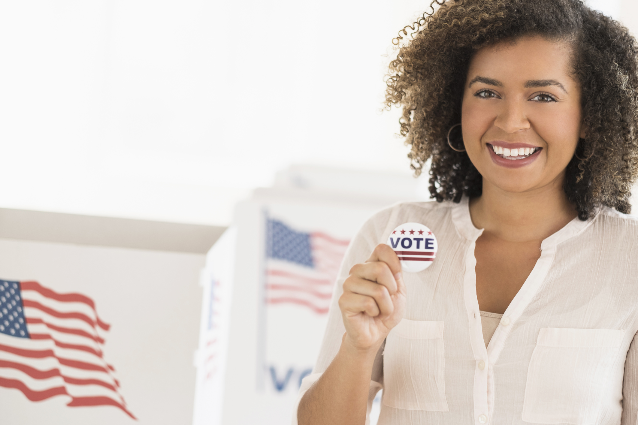 Young woman holding voting badge and smiling