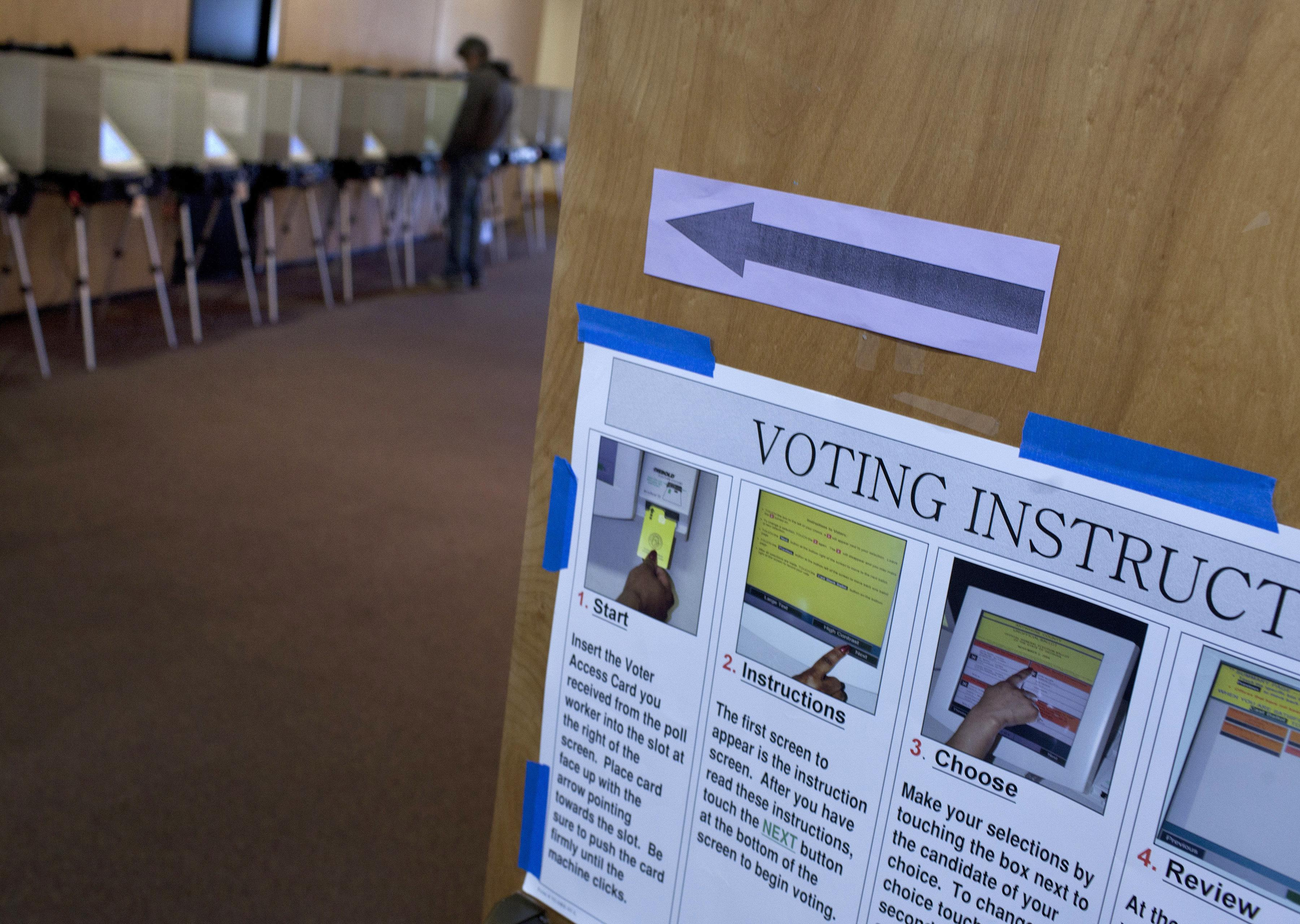 A voter casts his ballot at a voting mac