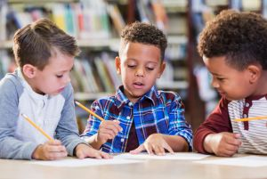 Three multi-ethnic boys in library writing at table