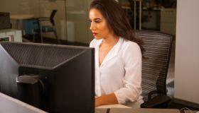 Latino Woman At Desk Side Shot